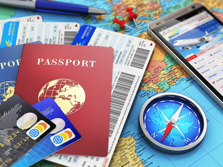 Travel concept with air tickets or boarding pass, passports, touchscreen smartphone with online airline tickets booking or reservation internet application, magnetic compass, credit cards and pen on world geographic map atlas