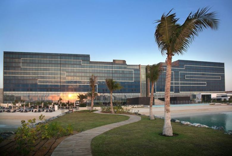 A view of the Fairmont Bab Al Bahr hotel in Abu Dhabi from the getty, with the setting sun reflecting on the windows and some waving palm trees and a winding path in front