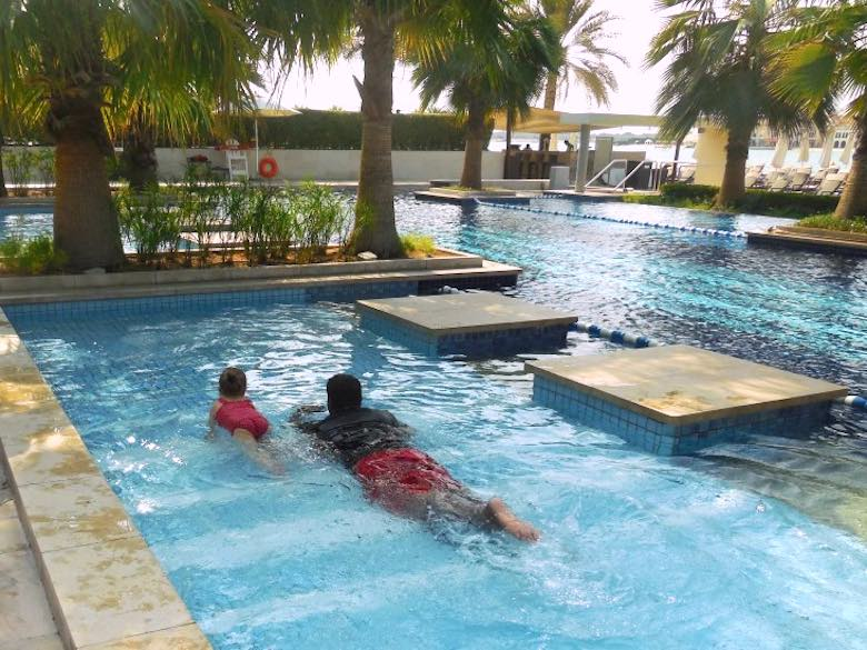 CosmopoliClan's Alegra taking swimming lessons from a staff member in the pool of the Fairmont Bab Al Bahr hotel in Abu Dhabi