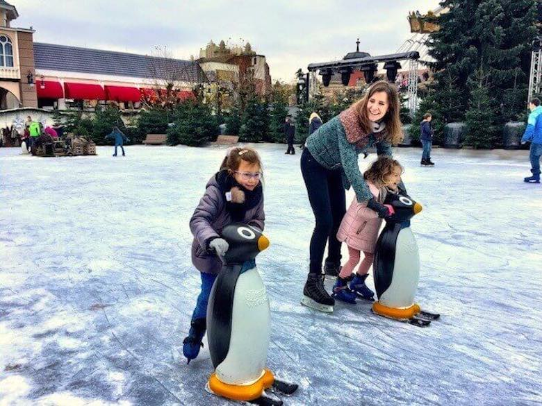Mother and two daughters ice-skating on the rink in Phantasialand in Brühl, assisted by a penguin pal