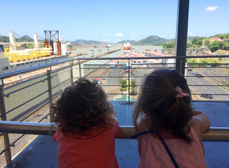 Two little girls spending a day at the Panama canal and watching the ships as they enter and leave the Miraflores docks