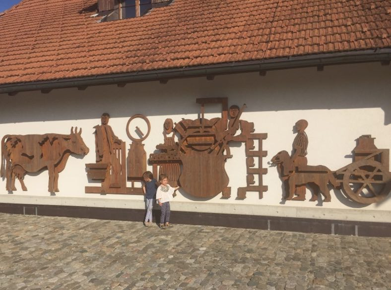 Two girls standing in front of the beautiful facade of the Emmentaler Schaukäserei or Emmental Showdairy in Affoltern, Switzerland