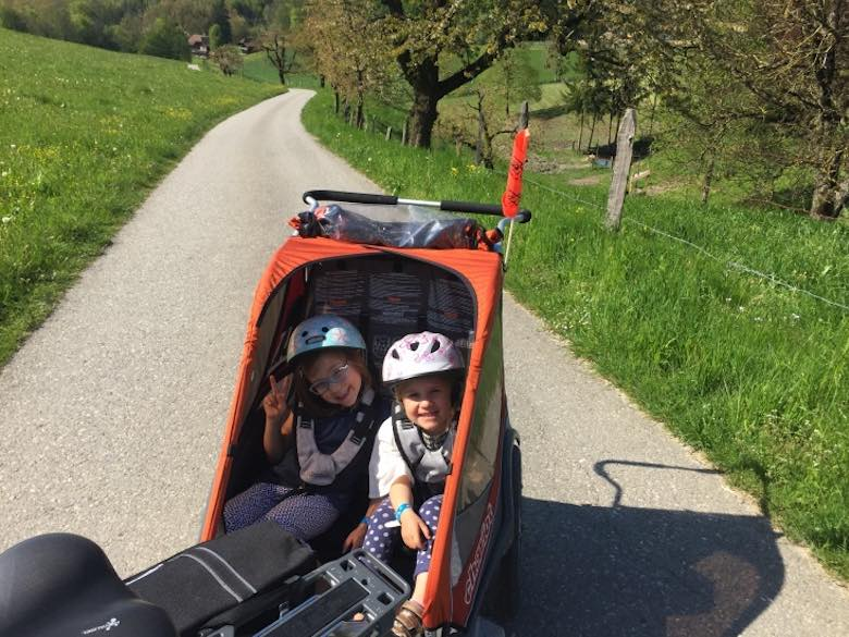 Two little girls in a bike trailer on a lush green hill, both smiling while they explore Emmental in Switzerland