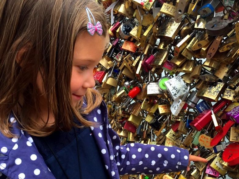 Reading the names on the locks in the Pont des Arts in the city of love Paris