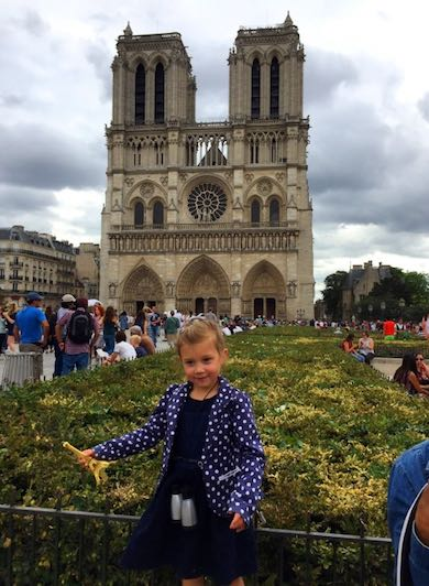 CosmopoliClan's little girl holding a miniature Eiffel tower in front of Notre-Dâme during a mother-daughter trip to Paris