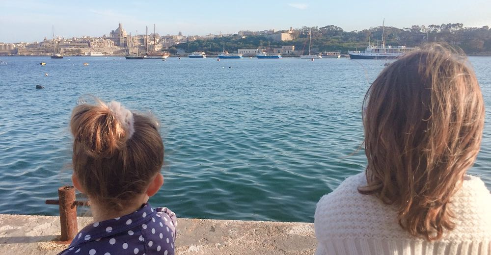 Two girls looking out over the water to Valletta from Sliema harbour
