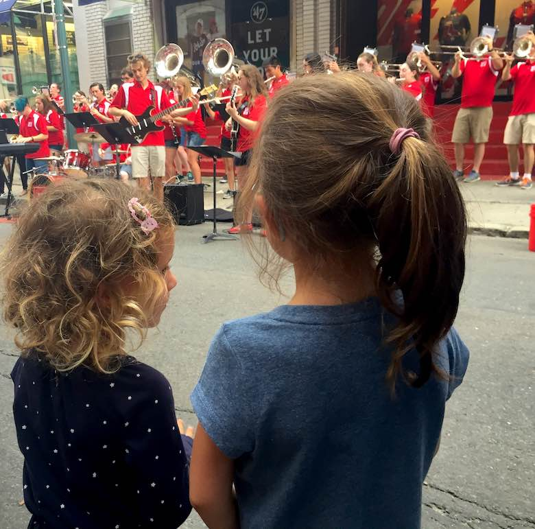 Two little girls standing with their back to the camera, looking at the red dressed music band before a red socks game in Fenway Park