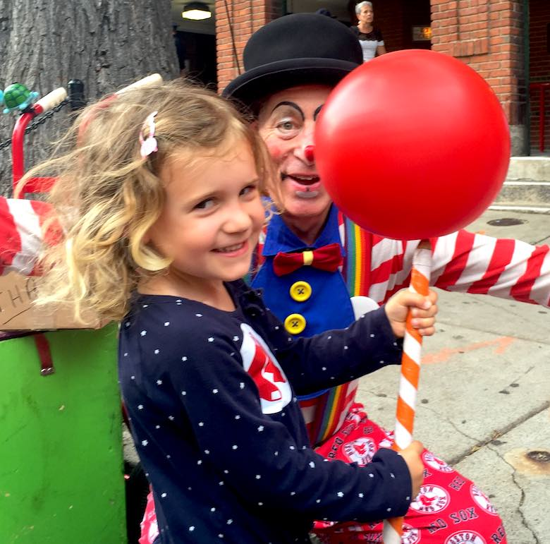 A little girl smiling brightly while holding red balloon on a white and red striped stick, under the approving eye of a red dressed clown before a red socks game in Fenway Park