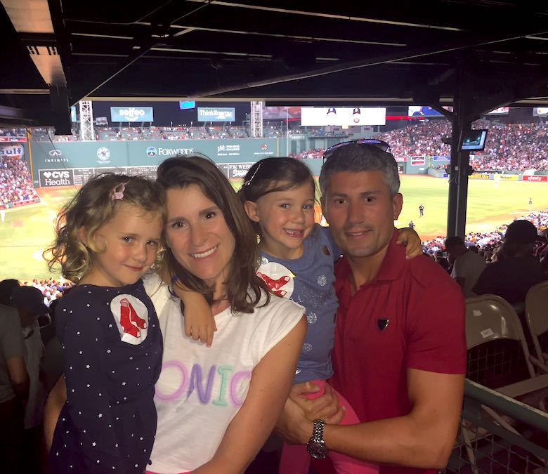 The CosmopoliClan family, dad, mom and two little girls, posing at Fenway Park during a Red Socks game