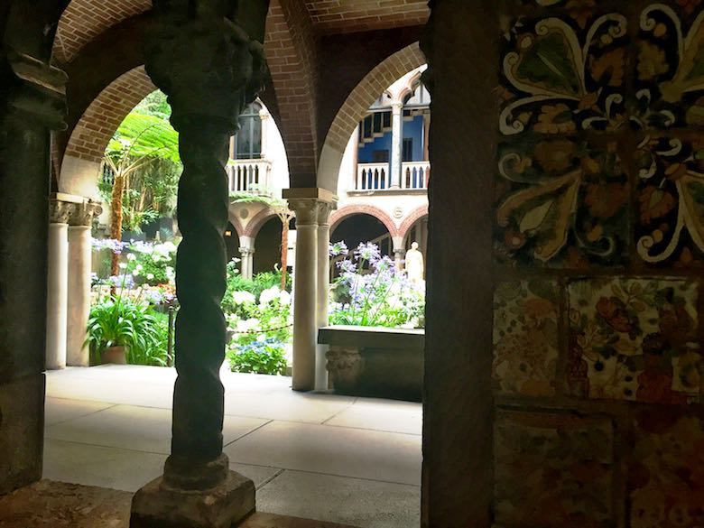 A view of the beautiful green courtyard of the Isabella Stewart Gardner museum, taken from an inside room with colourful walls