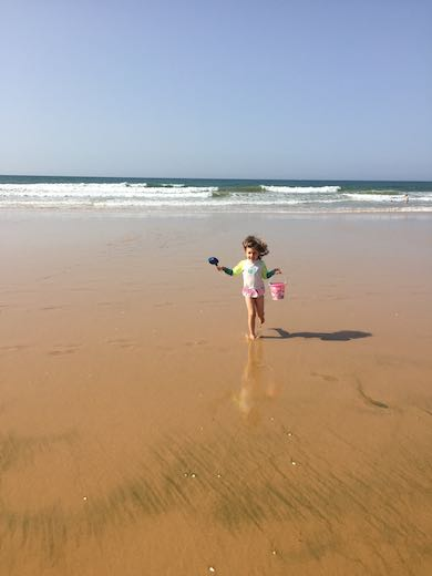 Little girl smiling brightly on the beach as she returns from the ocean in the Algarve with a bucket full of water