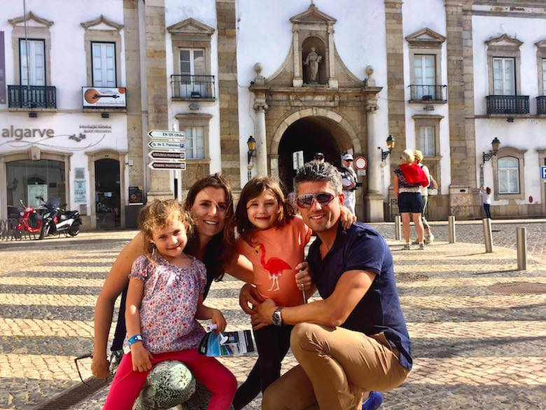 Family portrait in front of the arch (Arco da Vila) in Faro, the main entrance to the historic centre in authentic Algarve's regional capital