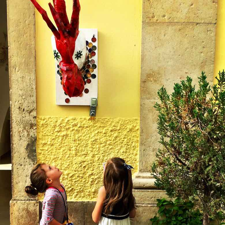 Two little girls admiring a red Galo de Barcelos artwork against a yellow wall in the streets of Loule in authentic Algarve in Portugal