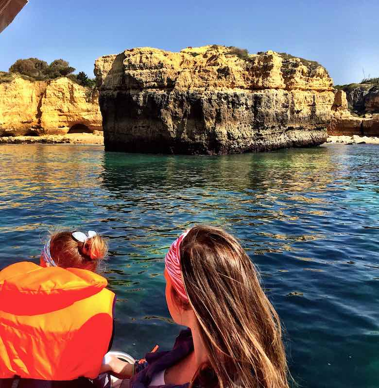 Rear view of a mother and daughter on a boat along the stunning coast of authentic Algarve in Portugal