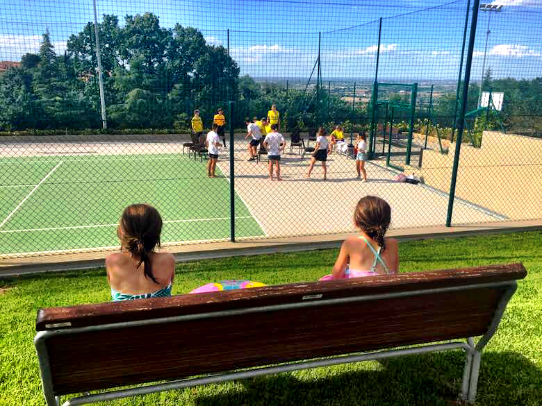 Two little girls sitting on a wooden bench and looking at a game on the tennis court on Palazzo di Varignana Resort & Spa near Bologna