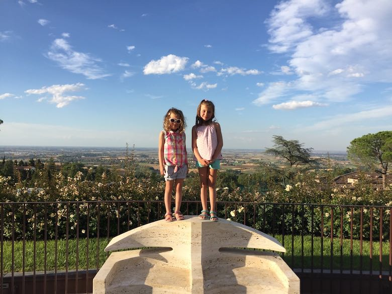 Two sisters, one with sunglasses, standing on a marble bench and posing in front of the mountaintop panorama at Palazzo di Varignana Resort & Spa near Bologna