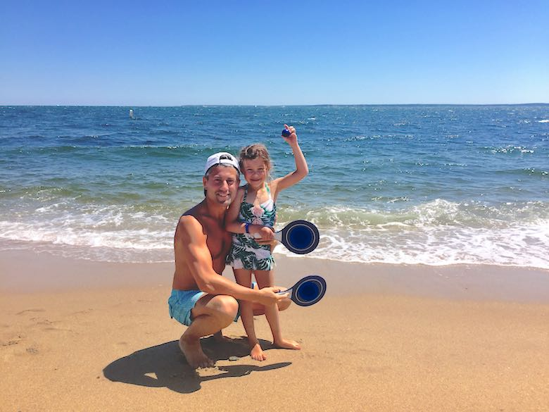 A little girl and her dad, posing with their pingpong rackets on the beach while celebrating the simple life in Cape Cod