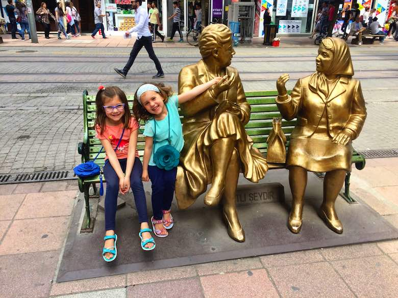 Two girls sitting on bench with two statues of talking women in the modern Turkish city of Eskişehir