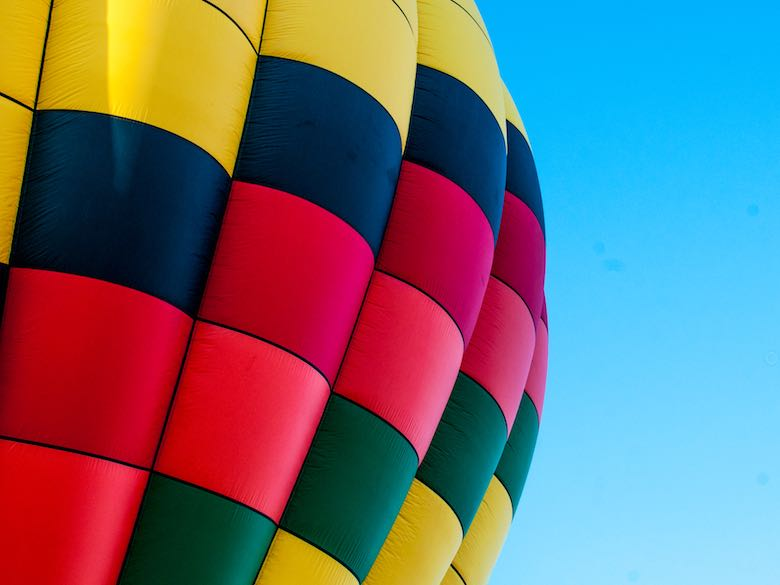 Sideview of a hot air balloon in bright colors against a clear blue sky