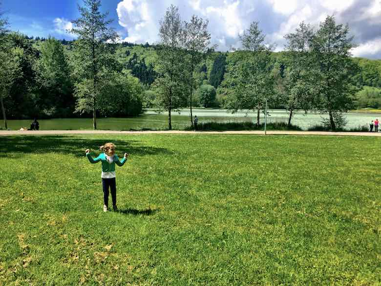 Happy CosmopoliGirl Jade on the grass field along the Echternach lake during a visit to Luxemburg with kids