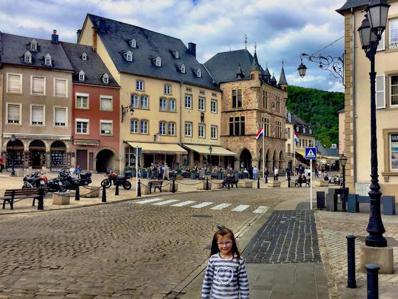 Little girl with striped sweater standing on the central square in Echternach during a visit to Luxemburg with kids