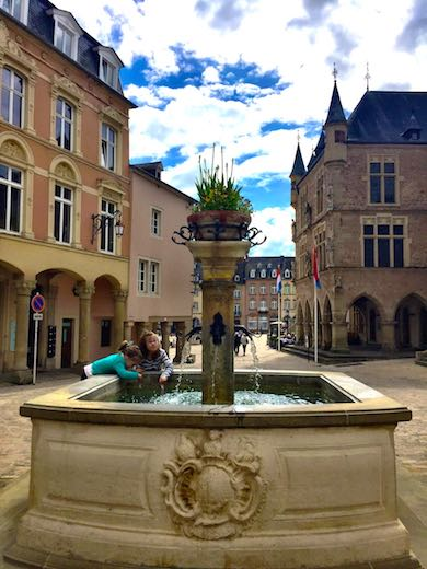 Two little girls playing in the fountain in the centre of Echternach in Luxemburg