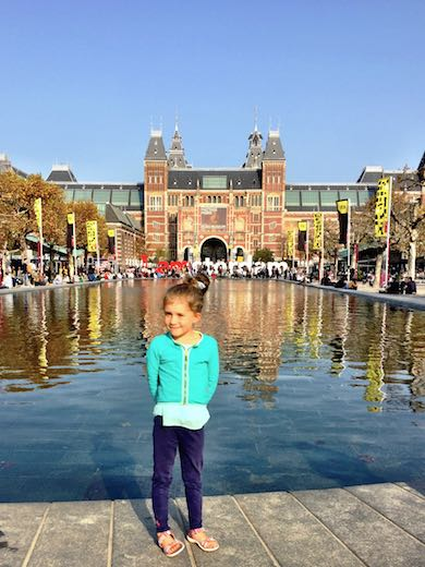 A little girl in green cardigan posing in front of the water basin, IAmsterdam letters and Rijksmuseum during a mother-daughter trip to Amsterdam