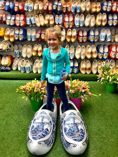 Little girl wearing giant clogs and posing in front of a wall full of regular sized clogs during a mother-daughter trip to Amsterdam