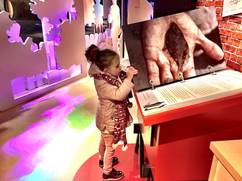 Een meisje in roze winterkledij slaat de bladzijde om van een reuzegroot boek in Ecomare op Texel