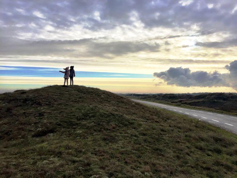 Twee kleine meiden op een heuvel in het Nationaal Park Duinen van Texel, wijzend naar de zee en met een mooi wolkenspel op de achtergrond