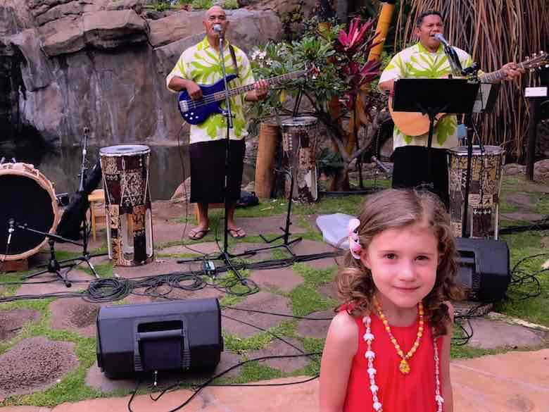 Little girl posing with the band at the Wailele Polynesian Luau