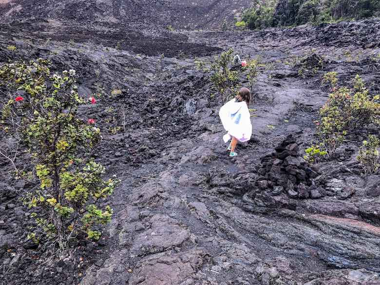 Little girl in poncho hiking the Kilauea Iki Trail on Big Island Hawaii