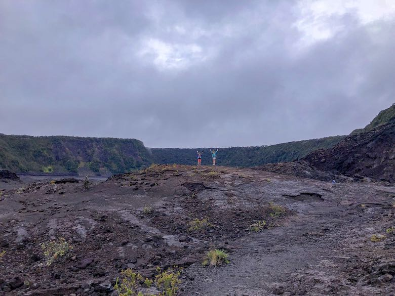Two little girls putting their hands in the air amid the black lava of the Kilauea crater in Hawaii Volcanoes National Park