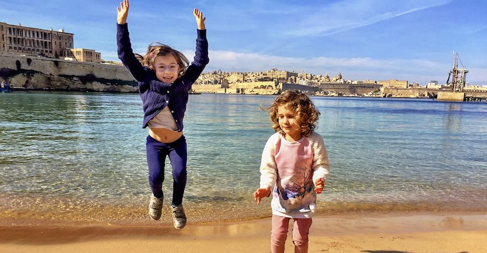 Two little girls jumping on the beach of Rinella Bay in Malta