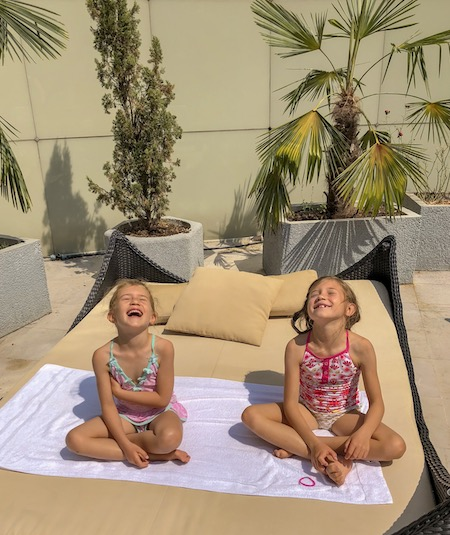Two little girls enjoying the sunshine on their face while sitting on a sunbed at the Deluxe Palace Family Room with garden view at the Trianon Palace Versailles, a Waldorf Astoria hotel's solarium