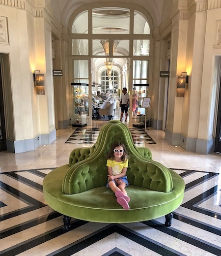 Little girl wearing sunglasses and sitting in the lobby of the Waldorf Astoria Trianon Palace Versailles