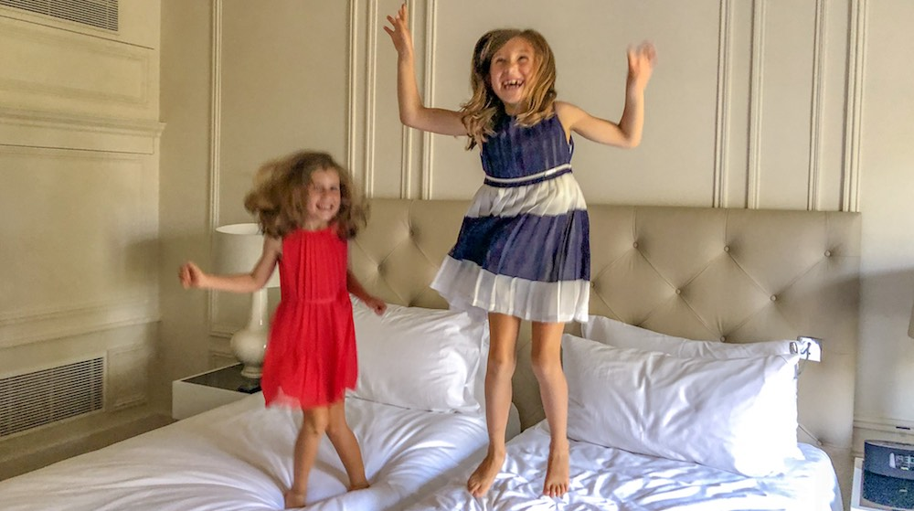 Two little girls jumping on the bed during their 4 nights Paris trip