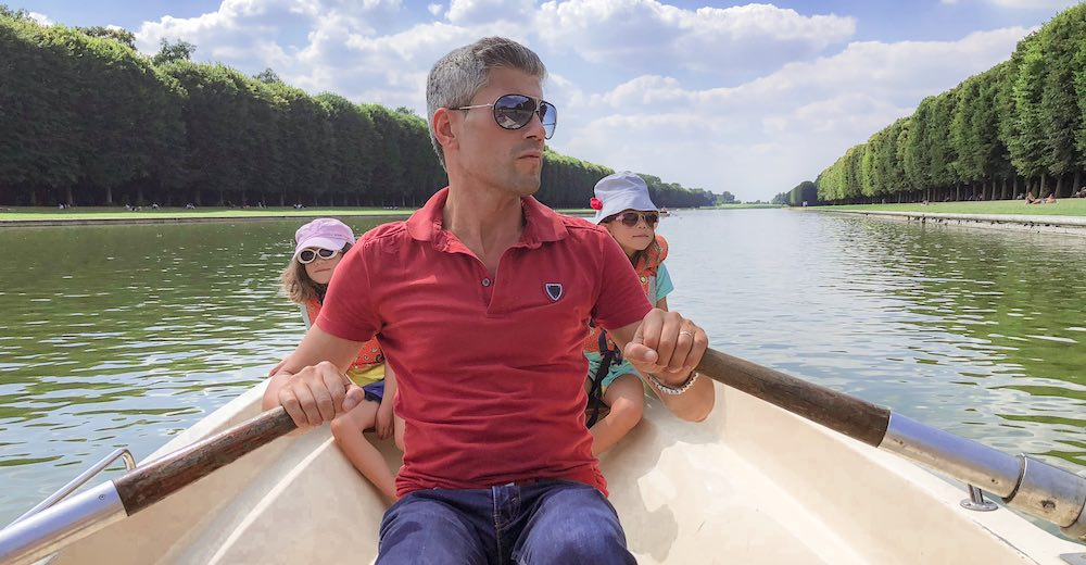 Renting a boat to row on the Grand Canale during a Paris to Versailles day trip