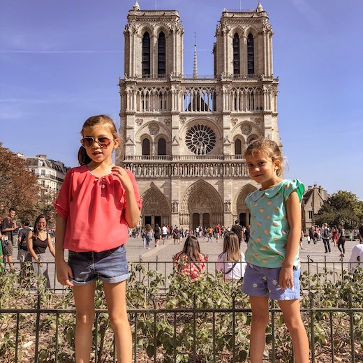 Little girls posing in front of the Notre Dame in Paris