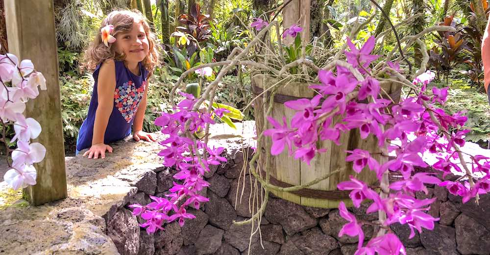 Little girl smiling at a water well with purple orchids at the Hawaii Tropical Botanical Gardens in Onomea Bay near Hilo Hawaii