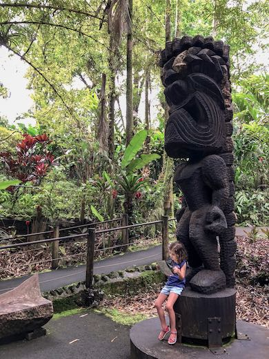 Little girl looking at the map while resting on a Tiki statue at the Lush nature surrounding the trail at the Hawaii Tropical Botanical Gardens in Hilo Hawaii