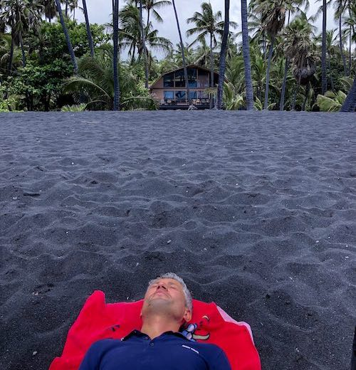 CosmopoliDad lounging on Pu'unalu black sand beach on Hawaii Big Island