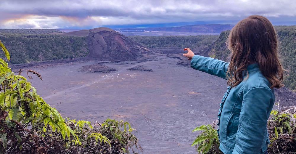 Klein meisje wijst naar de krater van een vulkaan in Volcanoes National Park, een hoogtepunt van onze reis naar Hawaii met kinderen