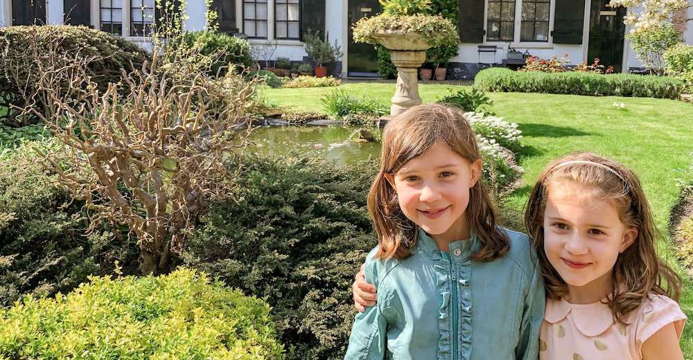 Two little sisters smiling in the courtyard of the Hofje van Bakenes, the oldest hofje and a must-visit in Haarlem Netherlands