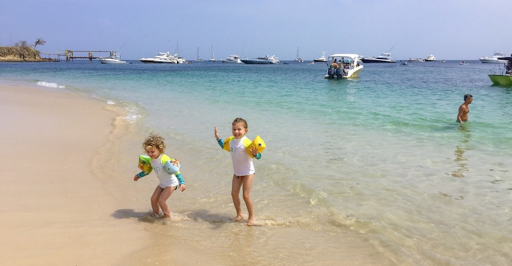 Two little sisters having fun at the surf of Contadora Island, the most popular of the Pearl Islands in Panama