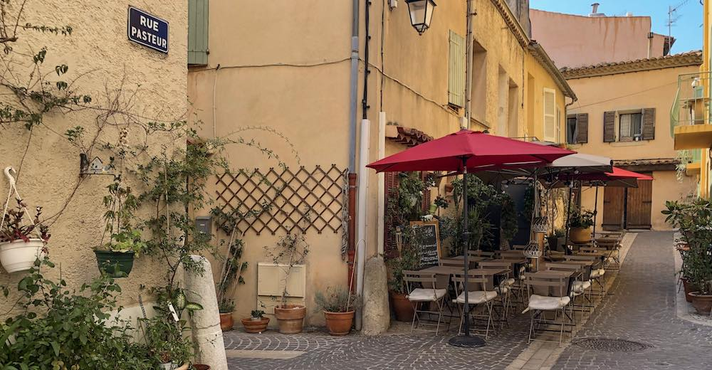 Narrow streets with pastel houses and quaint eateries in Cassis France