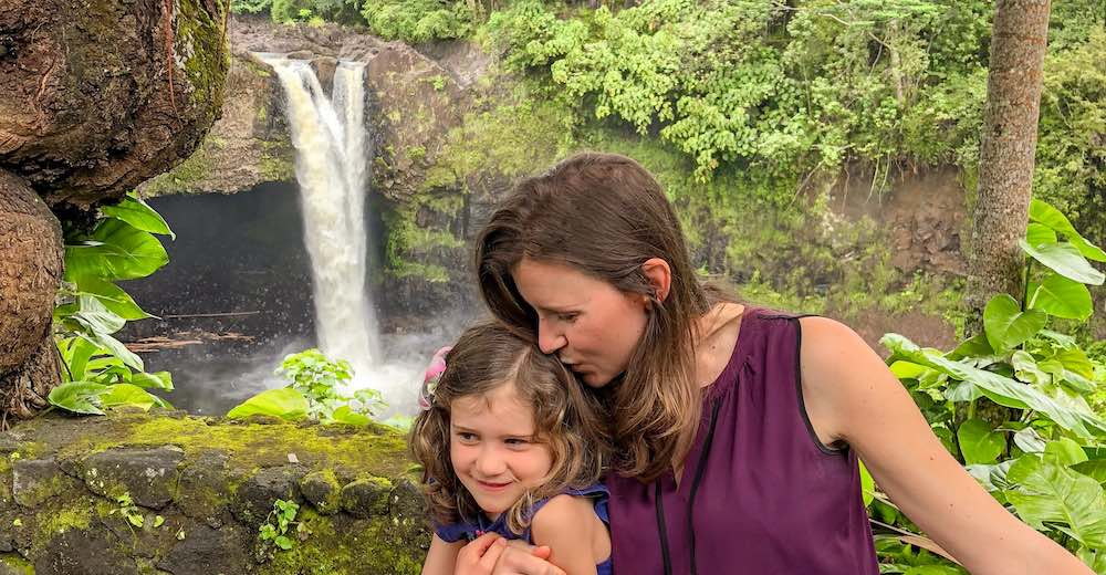 Mother kisses daughter at Rainbow Falls, one of the top attractions in Hilo Hawaii