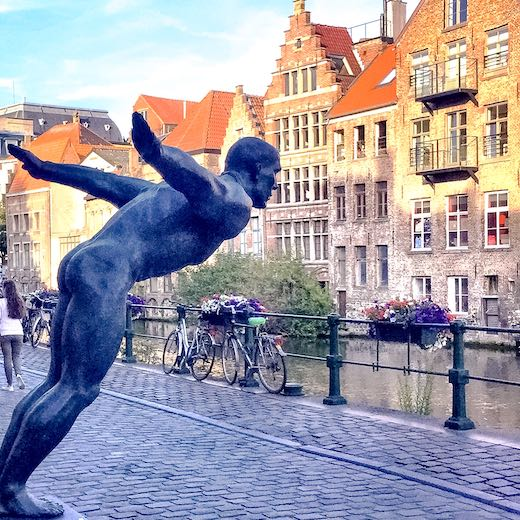 Sculpture of a diver in a charming cobbled street in Ghent, one of the best cities in Belgium