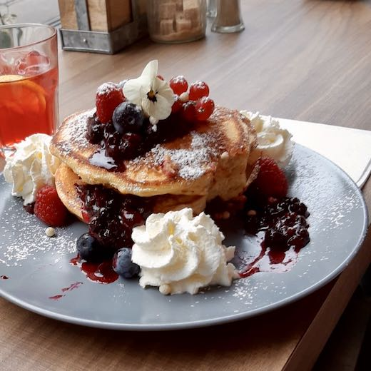 Bruges or Ghent for foodies - Stack of berry pancakes with dots of whipped cream in Ghent Belgium