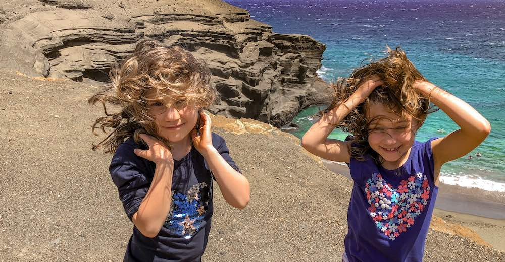 Two little girls with the wind in their hair at Papakolea beach Hawaii or green beach Big Island
